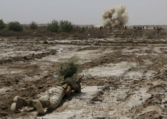 A member from the Iraqi security forces uses bushes as camouflage while smoke rises from a mock bomb as part of military training in Jurf al-Sakhar