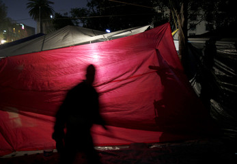 A teacher on strike casts his shadow as he stands inside his tent at the Plaza de la Republica in downtown Mexico City