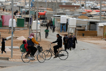 Syrian refugees ride bicycles on the main street of Al Zaatari refugee camp in Jordan, near the border with Syria