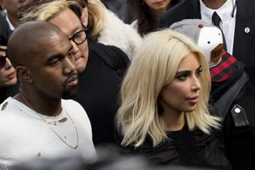 TV personality Kardashian and rapper West leave after French designer Ghesquiere's Autumn/Winter 2015/2016 women's ready-to-wear collection for fashion house Louis Vuitton during Paris Fashion Week