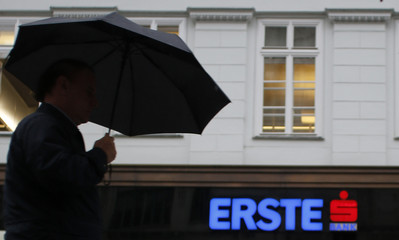 File photo of a man with an umbrella passing the entrance of the headquarters of Austrian Erste Group Bank in Vienna