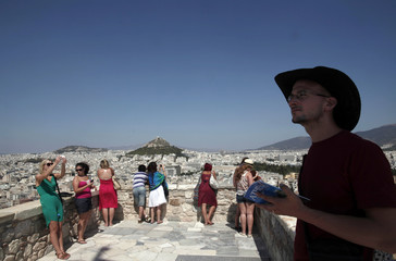 Tourists take pictures at the top of the Acropolis hill in Athens