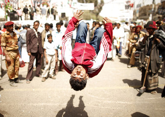 An anti-government protester jumps to entertain fellow protesters at Taghyeer (Change) Square in Sanaa