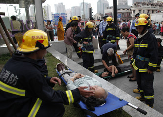 Rescue workers evacuate injured people outside Yu Yuan Garden station after a subway train collision in Shanghai