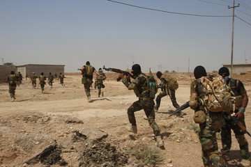 Asaib Ahl al-Haq Shi'ite militia fighters from the south of Iraq run during a mission to take control of Sulaiman Pek village from Islamist State militants, in the northwest of Tikrit city