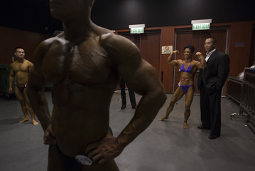 A female bodybuilder poses for pictures with a fan at the backstage before competing in the HKFBF International Bodybuilding and Fitness Invitation Championship in Hong Kong