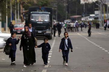 A woman walks with her children past police officers near the site of a series of explosions in front of Cairo University