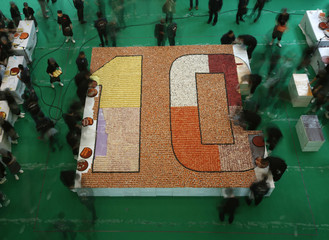Participants arrange sushi to create mosaic during 10th anniversary of a sushi chain store in Hong Kong