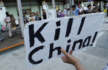 A protester holds an anti-China banner at a march denouncing South Korea and China in Tokyo