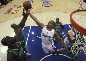 Los Angeles Clippers Randy Foye fights for a rebound with Boston Celtics Kevin Garnett and Paul Pierce during their NBA basketball game in Los Angeles