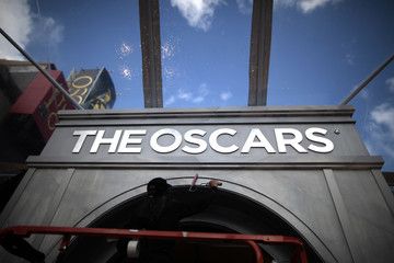 A worker puts finishing touches to an Oscar archway during preparations for the 83rd Academy Awards in Hollywood