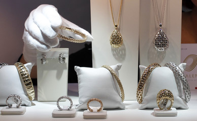 Staff member takes piece of jewellery from stand at Valenza international jewels exposition in Valenza