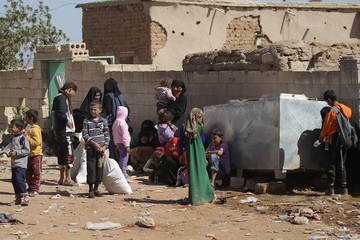 Civilians, who fled from Islamic State-controlled areas, wait at a checkpoint controlled by rebel fighters of the 'Sham Legion' in the northern Syrian rebel-controlled town of al-Rai, in Aleppo Governorate