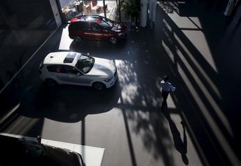 A dealer walks past cars displayed at BMW's dealer shop in Beijing