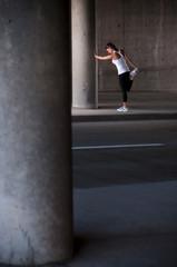 Runner stretching on sidewalk