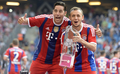 Bayern Munich's Claudio Pizarro (L) and Rafinha pose with the trophy after their German Telekom Cup soccer final match against VfL Wolfsburg in Hamburg,