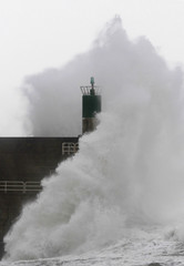 A wave breaking against a lighthouse in La Guardia, northern Spanish region of Galicia