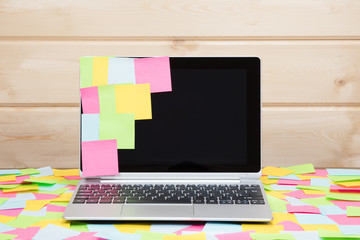 Colorful sticky notes stuck to a laptop screen