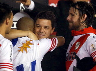 Marcelo Gallardo, head coach of Argentina's River Plate, celebrates with players Carlos Sanchez and Fernando Cavenaghi after they defeated Mexico's Tigres and clinched the Copa Libertadores tournament at Monumental stadium in Buenos Aires