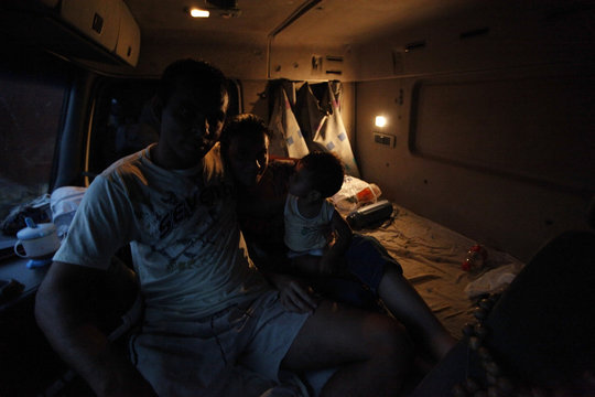 Truck driver Correia and his family sit inside the cab of their truck as they wait to unload their cargo of cereal grain in Alto de Araguaia