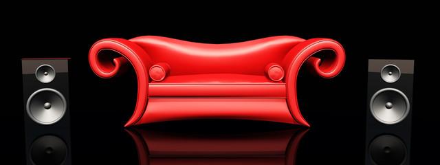 Rotes Sofa und Lautsprecherboxen vor schwarzem Hintergrund