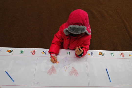 A child draws his wishes on the world's longest letter addressed to Santa Claus during a Guinness World Record attempt in Pantelimon