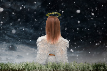Engel kniet im dichten Schneefall im Gras und betet