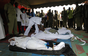 A paramedic officer arranges recovered bodies from the ferry tragedy for identification at the Maisara grounds in Zanzibar
