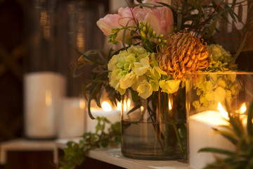 Romantic decor: glass vase with flowers in it, lit candles around it. Dim lights from candles only. Night time. Rich interior. Warm toning