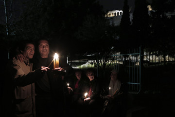 People light candles during a rally as the Parthenon temple is pictured in the background in Athens