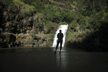 Woman takes a photo of the Waimea waterfall on the North Shore of Oahu in Pupukea, Hawaii