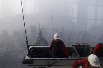 Workers clean the exterior of Shanghai World Financial Center amid heavy smog at the financial district of Pudong in Shanghai