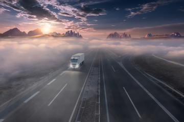 Lone truck on misty highway at idyllic sunny morning