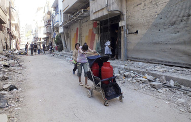 A girl pushes plastic containers of water past rubble and damaged buildings in a sieged area of Homs