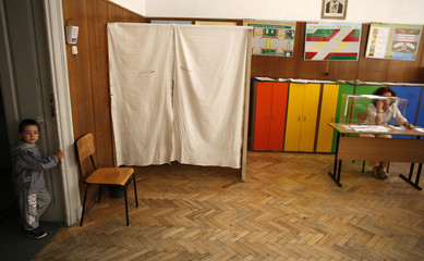 A boy waits as his mother casts her vote at a polling station in Sofia