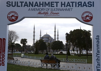 A couple sits on a bench, with the Ottoman-era Sultanahmet mosque, known as the Blue mosque seen in the background, at Sultanahmet square in Istanbul, Turkey