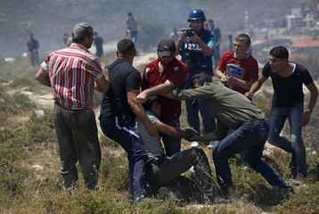 Palestinians gather around a man injured by a tear gas canister fired by Israeli troops during clashes near Nablus
