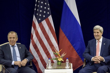 Russia's Foreign Minister Lavrov and U.S. Secretary of State Kerry sit next to each other before a bilateral meeting in Kuala Lumpur