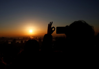 A man takes picture of  the first sunrise on New Year's Day at Roppongi Hills observation deck in Tokyo
