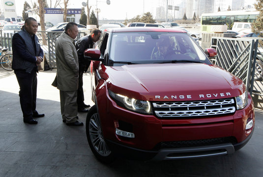 Customers look at a Range Rover Evoque car outside a dealership in Beijing