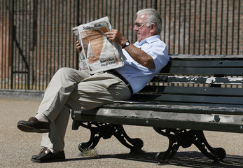 A man reads copies of Daily Mail newspaper featuring a picture of the newborn baby of Catherine, Duchess of Cambridge and Britain's Prince William, at Kensington Gardens in London