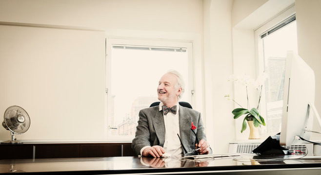 Senior businessman at desk, smiling
