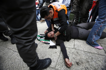 A Palestinian protestor is treated by Palestinian medical personnel after being injured during confrontations between Israeli security forces and Palestinian protestor near Damascus Gate at Jerusalem's old city