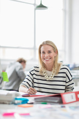 Young woman sitting at desk and smiling in creative office, portrait