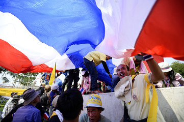 Anti-government protesters hold a large Thai flag as they climb over the reinforced barriers outside Government House in Bangkok