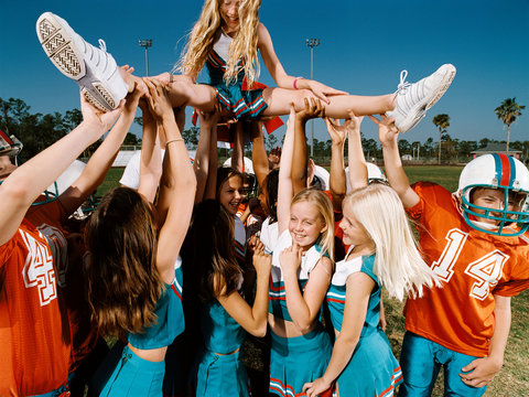 Cheerleaders and American football players lifting young woman