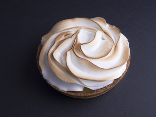 French lemon pie with meringue on top isolated on black background