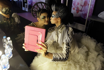 Models use an iPad to take a photo backstage before the MGPIN collection show by Maogeping Image Design Art School at China Fashion Week in Beijing,