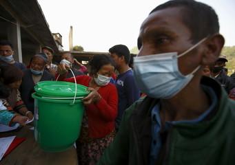 A woman heads back after receiving a hygiene kit following Saturday's earthquake at Sankhu, outskirts of Kathmandu