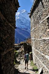 Woman treks through medieval stone buildings, Ghyaru, Nepal